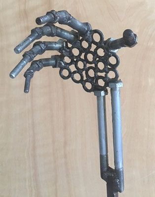 The hand is craftedx from nuts and bolts.
