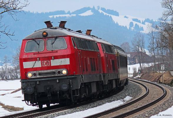 218 403 und 218 422 bringen am 02. März 2019 den EC 195 nach München, hier bei Trieblings am Alpsee.