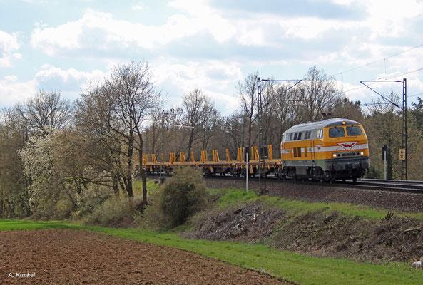 216 012 der Baufirma Wiebe hat einen leeren Langschienenzug am Haken, als sie Assenheim am 08. April 2016 aus südlicher Richtung erreicht.