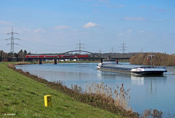 """Als RB 15713 nach Aschaffenburg am 26. März 2016 den Main überquert, ist das Motorschiff """"Gratias"""" gerade auf dem Main unterwegs. Es wird gleich in den Stockstädter Hafen einfahren, um dort seine Ladung zu löschen."""