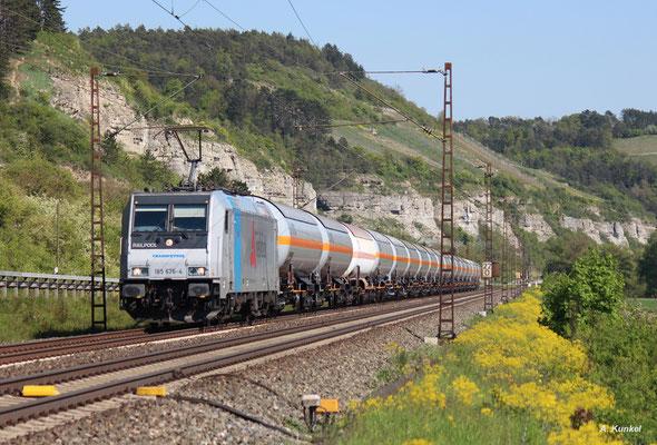 185 676 bringt im Einsatz für VTG Rail-Logistics einen Gaskesselzug durchs Maintal. Im Hintergrund die markanten Felsen bei Karlstadt.