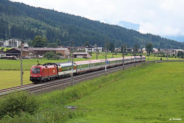 1116 164 hat EC 163 Zürich - Graz am Haken, als er am 06. August 2016 bei Kirchdorf in Tirol seinem nächsten Halt Kitzbühel entgegen fährt.