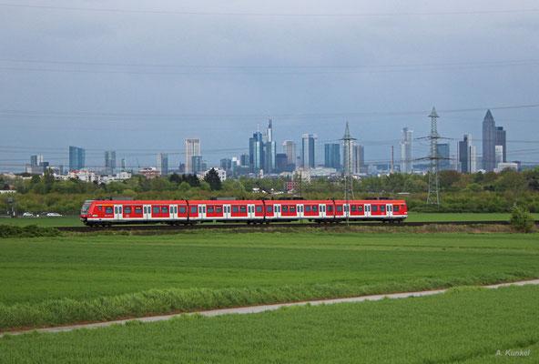 Ein 423 auf der Linie S5 zwischen Rödelheim und Steinbach vor der Skyline von Frankfurt, 15. April 2017.
