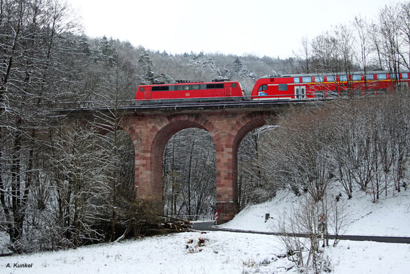 RE 4607 wird an diesem 18. Januar als 111-Sandwich gefahren. 111 214 ist die führende Lok, am Zugschluss hängt noch 111 179. Auf dem Laufweg des Zuges liegen auch die für die Spessartstrecke  typischen Sandsteinbrücken, wie hier bei Krommenthal.
