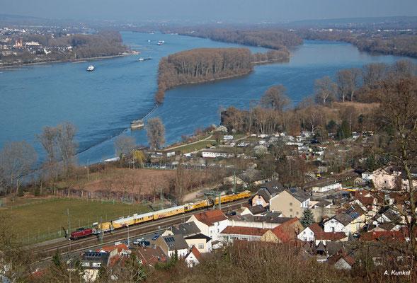 Eine V100 ist am 17. März 2016 mit einem Bauzug im Rheintal unterwegs. Sie erreicht soeben Bingen.