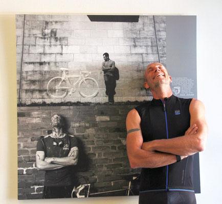 """Kai Hundertmarck vor seinem Portrait aus der Fotoausstellung """"Die Welt hat Pedale"""" von Rainer Kraus"""