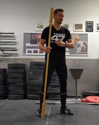 Andreas zeigt eine aus Holz gefräste Übungshantelstange von Good Mood Sports: perfekt zum Erlernen von Reißkniebeugen