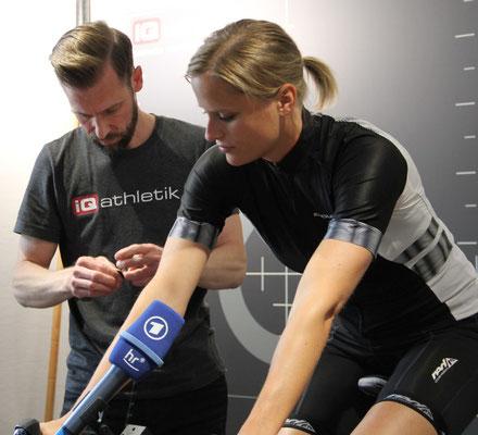 Für ein milimetergenaues Vermessen der Sitzposition auf dem Rad wird die Sportlerin mit Marken versehen, die dann von Higtech-Sensoren erfasst werden.