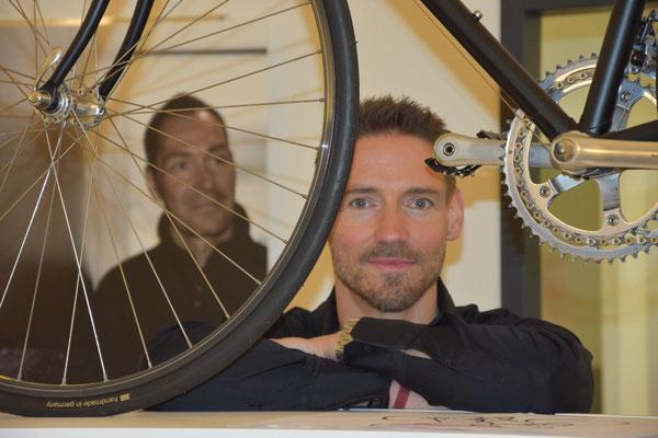 Radfahrer im Fokus der Linse: Andreas Wagner (Mitbegründer von iQ athletik) und Erik Zabel (Teil der Bilderausstellung)