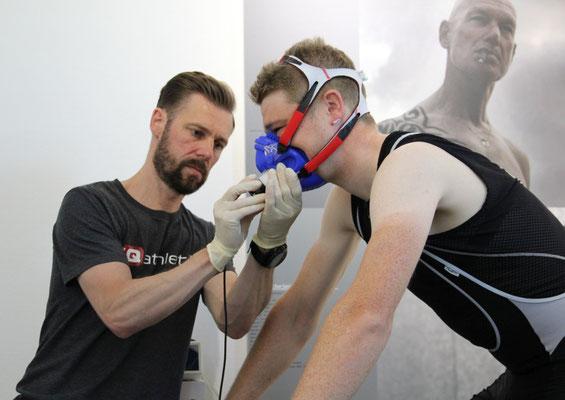 Der Leistungsdiagnostiker legt dem Radsportler eine Maske über Mund und Nase zum Durchführen einer Spiroergometrie