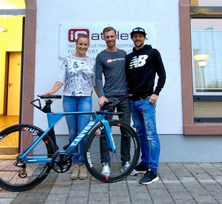 Der Triathlonprofi Patrick Lange (rechts) mit den iQ athletik Mitarbeitern Laura-Sophie Usinger und Sebastian Mühlenhoff