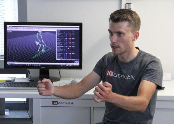 Der Bikefitter gibt Hinweise zur Körperhaltung, während der Sportler sich als visualisiertes Skelett auf einem großen Bildschirm sieht, das sich simultan zu den eigenen Bewegungen bewegt