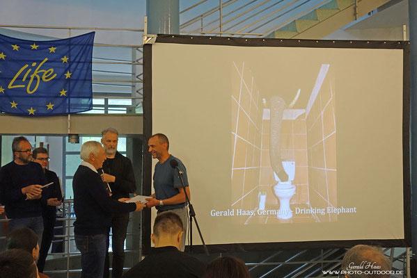 Der Cairman Marjan Artnak der Association of Slovenian Nature Photographers verteilt die Auszeichnungen.