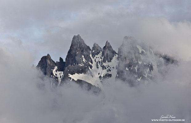 Ein Wolkenfenster gibt den Blick auf ein paar Gipfel der Dolomiten frei.