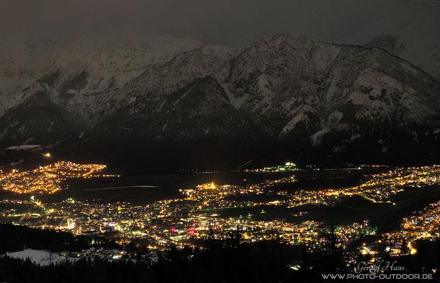 Nachtaufnahme des Inntals. Erst eine Langzeitbelichtung mit der Kamera macht die schneebedeckten Berge im Hintergrund sichtbar, für das menschliche Auge waren sie nicht wahrnehmbar!