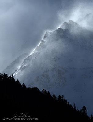 Ein Höhensturm treibt den Schnee über den Gebirgskamm.