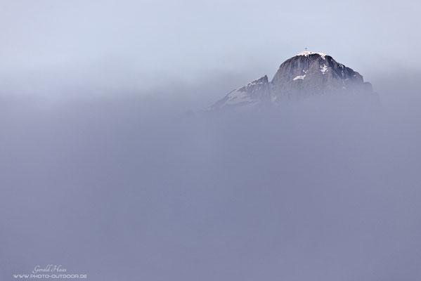 Der erste Dolomitengipfel taucht über dem Nebelmeer auf.