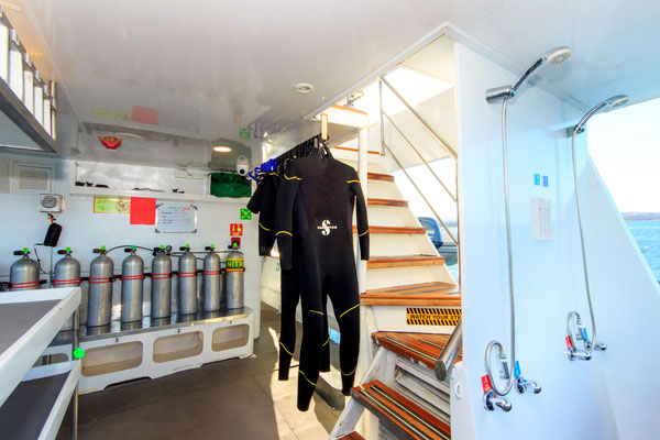 Wetsuits hanging on the dive deck of the vessel Galapagos Dive Expedition