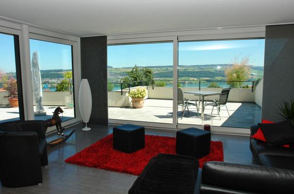 Der Wohnbereich mit um's Eck laufender raumhoher Fensterfront und entsprechend herrlichem Ausblick