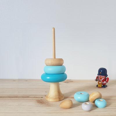 jeu en bois réalisé à la main en France. pyramide d'éveil empilable avec 7 donuts de coloris bleu tendre pastel et bleu miami plus soutenu