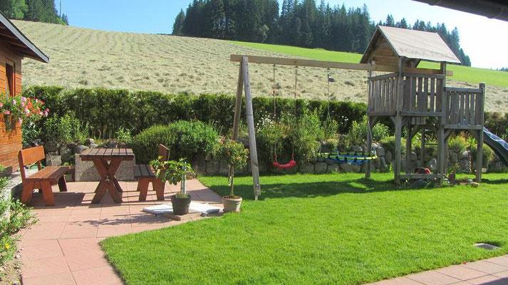 Gartenbank mit kleinem Spielplatz hinter dem Haus