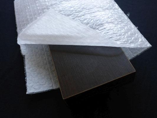 化粧板を不織布をラミネートしたエアセル製袋品(不織布ラミ製品)で梱包した様子。