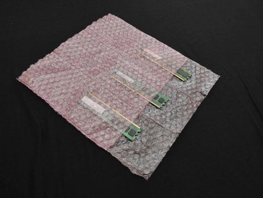 EP-100(帯電防止/二層品)の三連袋で基盤を梱包する様子。