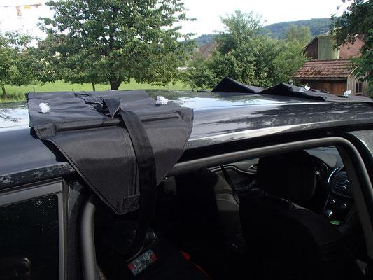 Dachträger ausrollen und je bei vorderen und hinteren Türen auf Dach auslegen