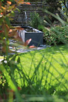 Beton Wasserbecken mit Vogeltränke und Wasserspiel vor natürlichem Holz Sichtschutz aus Rundholz