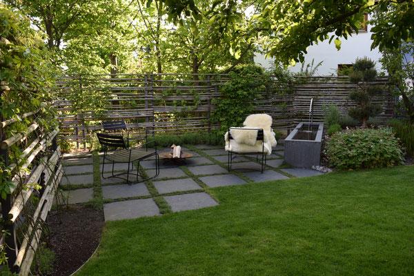 Holz Sichtschutz natürlich und individuell gebaut mit Feuerstelle davor und Beton Wasserbecken
