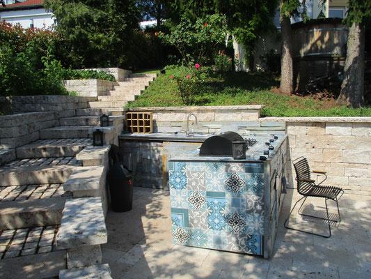 Outdoorküche Mosaikfliesen mit Grill und Herd auf Natursteinterrasse Travertin