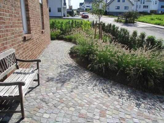 Natustein Granit mix Porphyr Basalt Einfahrt Gartenweg mit Pflanzung Gräser Kirschlorbeer