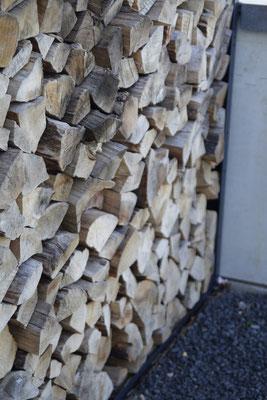 Holzlege Holzlager aus Aluminium Anthrazit RAL 7016 an Feuerstelle auf Basalt Zierkies Fläche