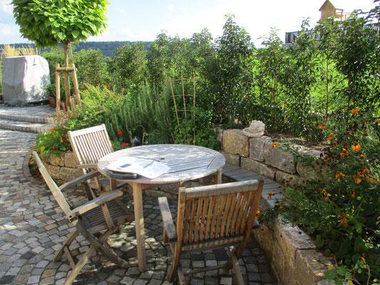 Terrasse aus Naturstein Granit Kleinpflaster mit Sitzbank aus Terrassenholz und Hochbeet Naturstein Muschelkalk