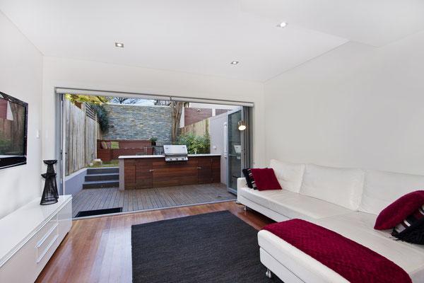 Kleiner Garten mit Outdoorküche aus Holz, Sitzpodest aus Terrassenholz, kleine Rasenfläche und Holz Sichtschutz