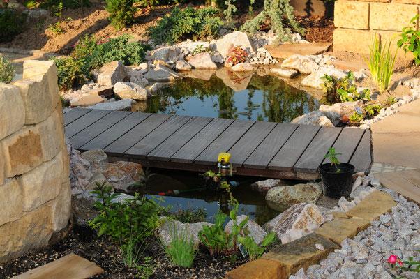 Gartenteich mit Holzbrücke neben Hochbeet aus Jurakalk Natursteinmauer