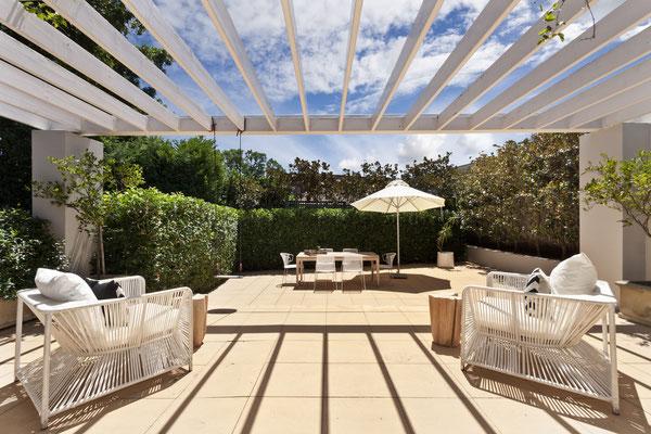 Kleiner Garten Gartengestaltung mit großer Terrasse aus Betonplatten und Heckenpflanzung aus Kirschlorbeer
