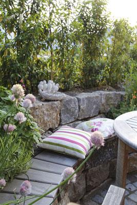 Muschelkalk Natursteinmauer mit Allium und Kräuterbeet terrassiert und Sitzbank aus Holzdeck