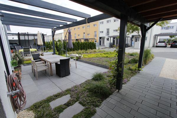 Terrasse mit Keramikplatten und Holz Pergola umgeben von Kräuterbeet und Beetbepflanzung aus Thymian Duftrasen und Gräser