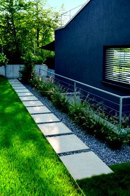 Trittplatten Betonplatte in Zierkies Fläche Basalt und Pflanzung aus Gräsern