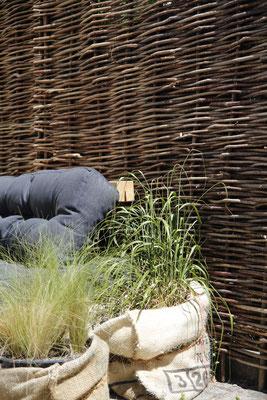 Natürlicher Sichtschutz aus Holz Haselnuss mit Outdoormöbeln Palttenmöbel und Gräser