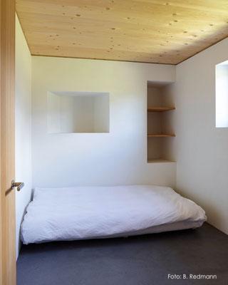 Schlafzimmer mit Kalkputz und schwarzem Betonboden, Alp Flix