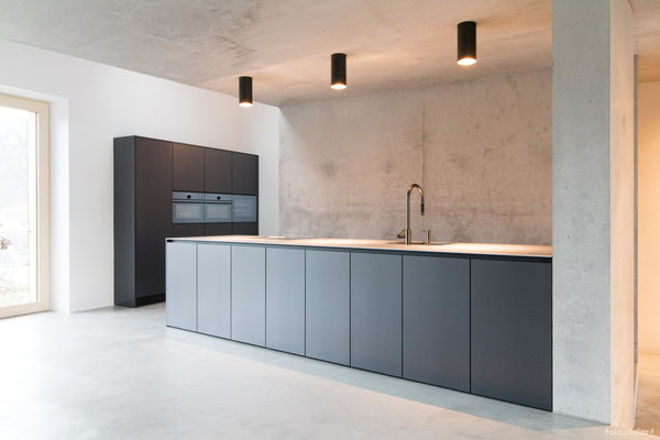 Küche mit Sichtbetonwand und Betonboden