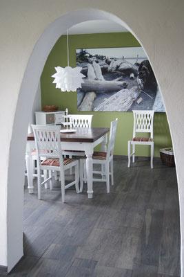 Blick von der Küche auf den Essplatz durch den offenen Türbogen, der Tisch kann auf beiden Seiten ausgezogen werden
