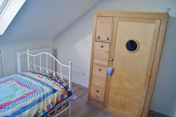 Das kleine Schlafzimmer im Dachgeschoss verfügt auch über einen Schrank für Kleidung.