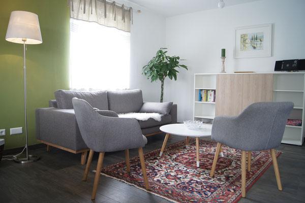 Schickes Wohnzimmer mit bequemem Sofa, hinter den Holztüren des Boards befindet sich der flache Fernsehbildschirm