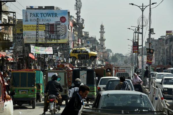 Straßenbild in Rawalpindi: das gelbe Auto wird von der Polizei mit einem Gabelstapler abgeschleppt