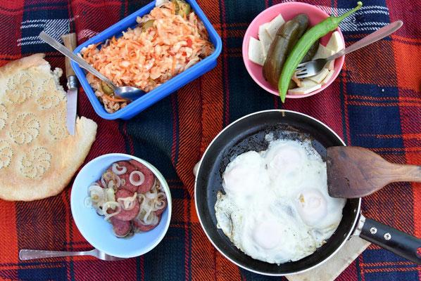 turkmenisches Essen: Krautsalat, saure Gurken, Käse, Wurst, Paprika, Spiegelei und Brot (zum Runterspülen gabs Bier)