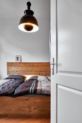 Das Bett aus altem Bauholz. Die Lampe aus dem Vintagestore.