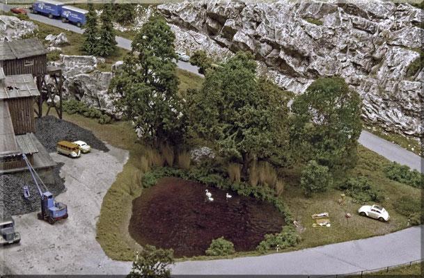 Der kleine Badesee am Fuße des Burgbergs, in unmittelbarer Nähe der Kohlemine. Bäume: Eigenbau aus Seemoos. Schilf: Gefärbte Pinselborsten. Wasser: Faller-Gießharz. Die Wellenhabe ich mit Window-Color auf-modelliert. Begrünung: Woodland- Scenics.